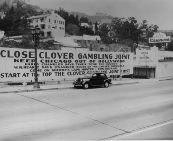 """Keep Chicago out of Hollywood- Close Clover Club Gambling Joint."""" Anti-gambling signs on a vacant lot owned by the Coyne family, adjacent to the Casanova Club, 8383 Sunset Blvd, c. 1837-1938. Similar signs located on vacant lots at 8381 and 8373 Sunset Blvd. mysteriously caught fire in the wee hours of Aug. 27, 1933. (Photo from L.A. Public Library)"""