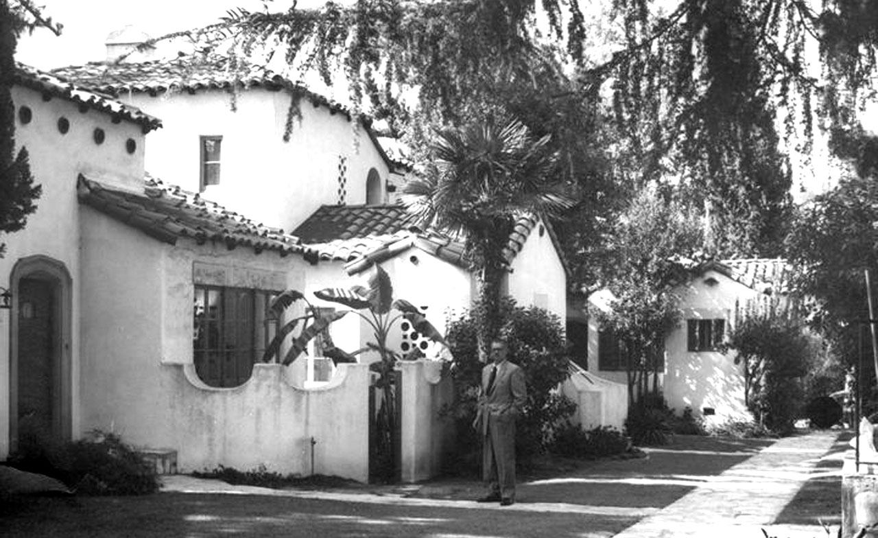 An unidentified man standing near the entrance to a row of villas
